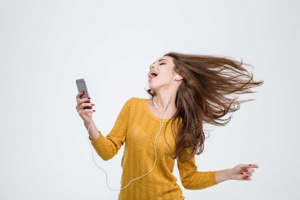 Portrait of a cheerful cute woman listening music in headphones and dancing isolated on a white background